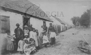 Former slaves in front of former slave cabins on St. Catherines Island, Georgia. Photograph taken between 1883 and 1892 by William E. Wilson